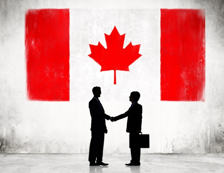 Two Businessmen Shaking Hands With Flag of Canada