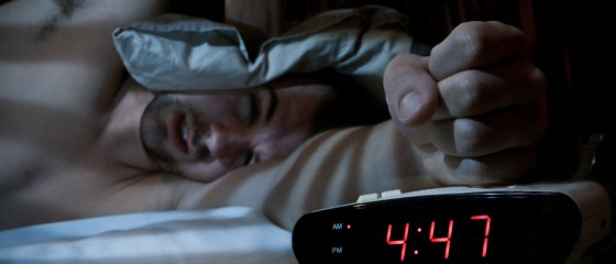 Unhappy man smashing the alarm clock.