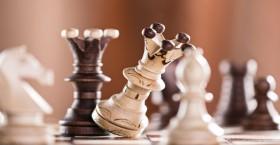 Black chess king crashes white chess king.