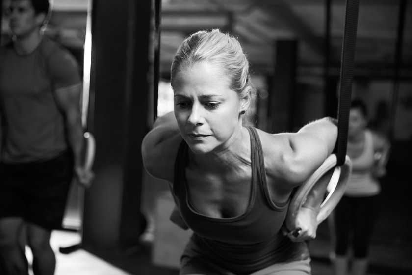 Black And White Shot Of Woman Using Gymnastic Rings In Gym