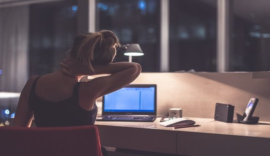 Young exhausted,depressed,concentrated woman sitting in office in the dark at the lamp.Studies late at night.Staying up late. Overworking. Feeling headache and pain in the neck