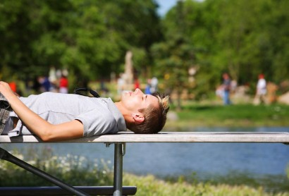 Man Laying On A Bench Near A Pond