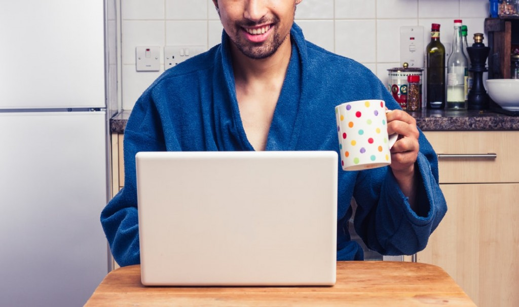 Man in robe checking emails and having coffee