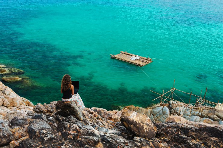 Woman freelancer feeling happy with laptop. Amazing seaview with blue lagoon with rocks.